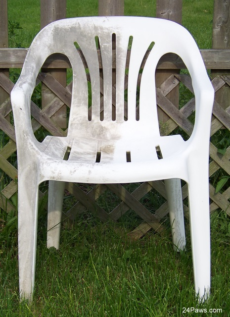 A resin chair heavily stained on one side and clean on the other.